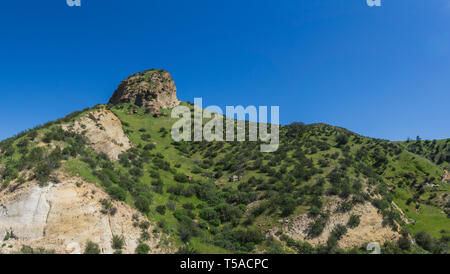 Rocky butte emerges from a grassy hillside in southern California near Santa Clarita. - Stock Image