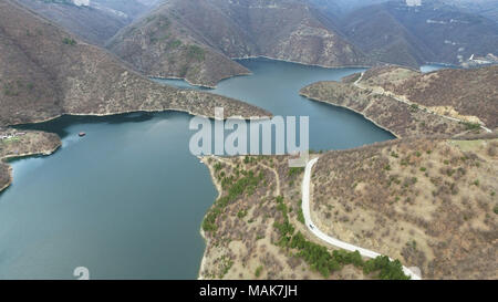 Aerial landscape view of a meandering big river lake and road in the mountain - Stock Image