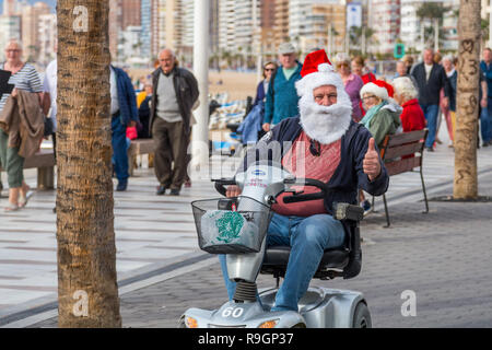 Benidorm, Costa Blanca, Spain, 25th December 2018. British tourists dress for the occasion on Christmas Day in this favourite getaway destination for Brits escaping the cold weather at home. Temperatures will be in the mid to high 20's Celsius today in this mediterranean hotspot.  Man on mobility scooter wearing Christmas clothing, santa hat and beard. - Stock Image