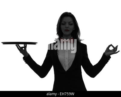 one  woman waiter butler holding empty tray zen gesturing in silhouette on white background - Stock Image