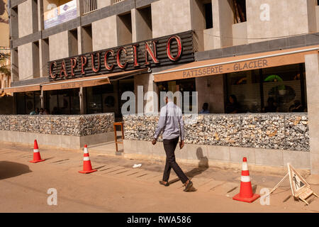 A man walks past the blast walkks protecting the Cappuccino restaurant and coffee shop in Ouagadougou in Feb 2019, three years after a terrorist attac - Stock Image