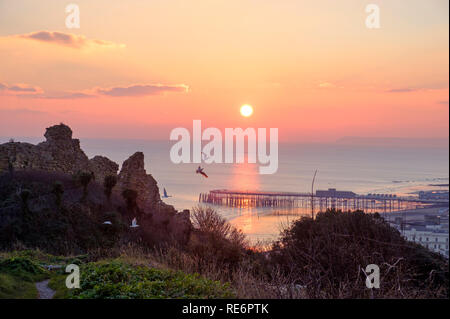 Hastings, East Sussex, UK. 20th January 2019. Seagulls fly from the Castle at sunset towards the pier at the end of a calm clear sunny day. - Stock Image