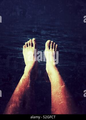 A pair of legs submerged into dark blue water - Stock Image