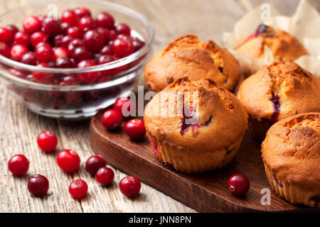 muffins with cranberries, cranberries in a glass bowl on the old wooden background - Stock Image