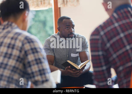 Attentive young man with bible in prayer group - Stock Image