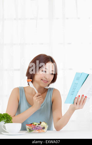 Young woman eating salad and looking away with smile, - Stock Image