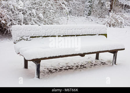 Wooden bench in snow - Stock Image