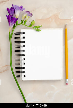 Flowers and blank notepad for text - Stock Image