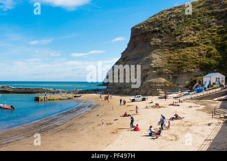 Holiday makers on the beach in the harbour at Staithes North Yorkshire UK on a warm summer day - Stock Image
