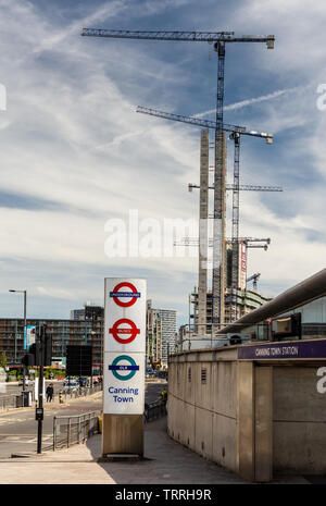 London, England, UK - June 1, 2019: Construction cranes tower over Canning Town London Underground and DLR station during a boom in high rise housing - Stock Image