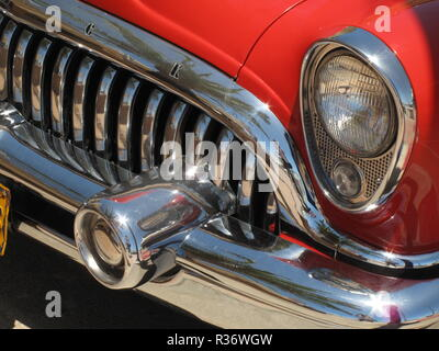 A shot of a headlight on a red retro car - Stock Image