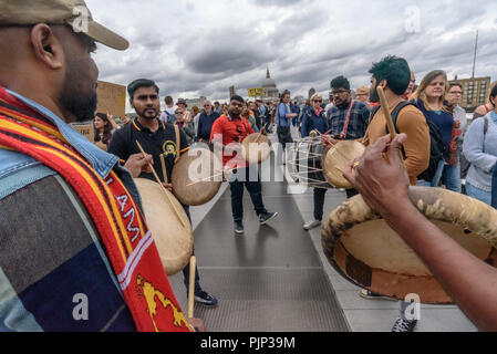 London, UK. 8th September 2018. Tamil drummers play as Climate Reality supporters pose for a photo on the Millennium Bridge at the end of their rally in front of Tate Modern, one of thousands around the world demanding urgent action by government leaders to leaders commit to a fossil free world that works for all of us. Credit: Peter Marshall/Alamy Live News - Stock Image