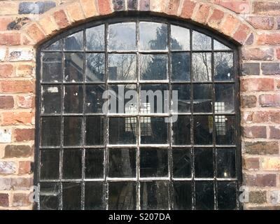 Old steel window, arched head, Crittal style, in an industrial workshop - Stock Image