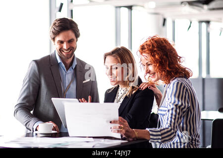 A group of young cheerful business people with tablet sitting in an office, talking. - Stock Image