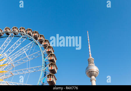 A ferris wheel is set up for one of many Christmas markets in Berlin, Germany. Berlin TV Tower in background. - Stock Image
