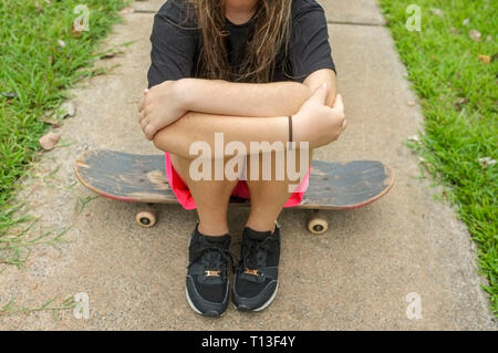 Unrecognisable teenage girl sitting on a skateboard. - Stock Image