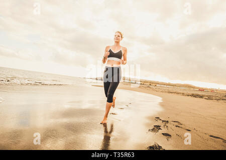 Beautiful blonde yong woman run at the beach to train and follow a healthy active lifestyle - enjoying running outdoor on the shore in barefoot way -  - Stock Image