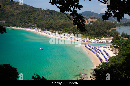 View over beach and bay with tourists on beach and in clear blue water Nai Harn near Cape Promthep - Stock Image