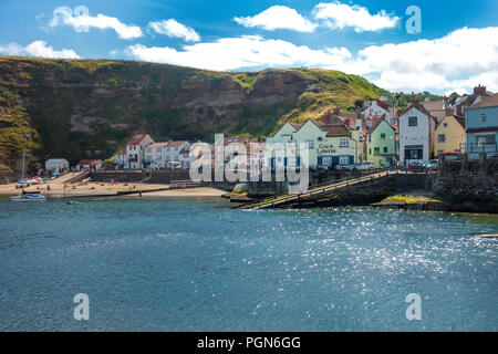 Staithes North Yorkshire beach and seafront across the bay on a bright sunny summers day - Stock Image