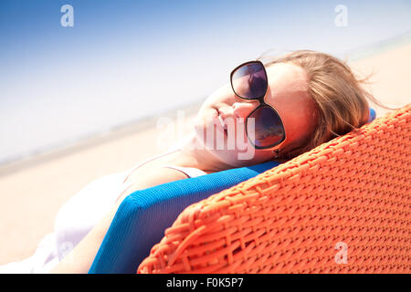 Young woman relaxes on a lounger on the beach - Stock Image