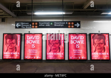 New York, USA. 121 April, 2018. A woman takes a selfie with one of the images of David Bowie on the Bleecker Street platform of the he Broadway-Lafayette subway station.  The installation, sponsorsed  by Spotify, is being held in conjunction with the exhibition 'David Bowie IS' at the Brooklyn. The subway installation is just blocks from where the late rock star lived in Soho. The art will be on display until mid May. ©Stacy Walsh Rosenstock - Stock Image