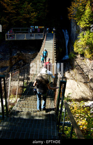 Pedestrians on suspension bridge over river gorge waterfall Canyon Ste Anne Park - Stock Image