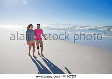 Front View Of Man With Artificial Leg Walking Along Beach With Female Partner On Summer Vacation - Stock Image