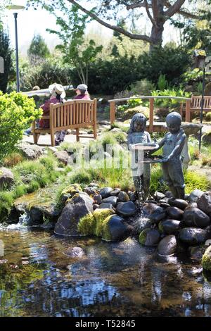 Two women sit on a bench near a statue of children playing, at the Oregon Garden in Silverton, Oregon, USA. - Stock Image