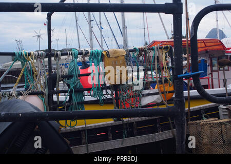 Ropes, netting a bag and knots tied on to the metal railings of a small fishing boat moored in Lochinver harbour, Scotland - Stock Image
