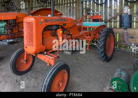 An Allis Chalmers tractor in a display of historic farm machineryat Ryedale Folk Museum in Hutton le Hole North Yorkshire England UK - Stock Image