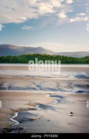 The River Nith, Dumfries and Galloway, Scotland. West across the tidal estuary mud flats on Solway Firth at Caerlaverock toward the mountain of Criffe - Stock Image