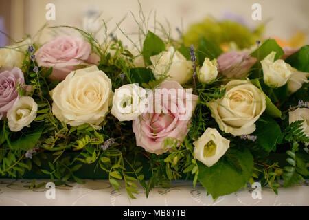 Large centerpiece with pastel color roses and fresh foliage  suitable as a decor for table centerpieces at weddings or formal events - Stock Image