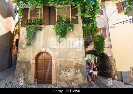 Tourists and shoppers walking along the narrow lanes and passages in the old town of Malcesine, Italy. - Stock Image