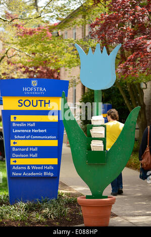 Hempstead, New York, U.S. - May 4, 2014 - A large blue wood tulip with holders for event flyers is next to a campus sign at the 31st Annual Dutch Festival, outdoors on the South Campus of Hofstra University, which features tulips in bloom throughout campus. A Long Island tradition. Credit:  Ann E Parry/Alamy Live News - Stock Image