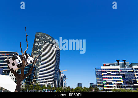 The Cow up a Tree sculpture in Melbourne Docklands.The Victoria Point Apartments and National Australia Bank headquarters is in the background - Stock Image