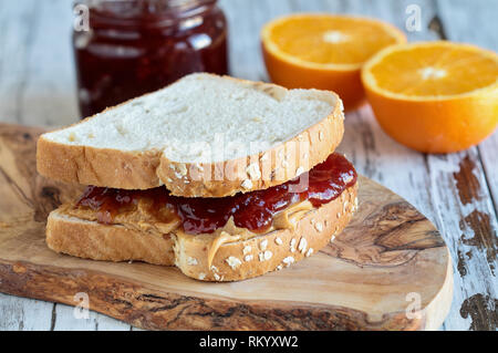 Homemade Peanut Butter and Jelly Sandwich on oat bread, over a rustic wooden background with fruit in the background ready for lunch. - Stock Image