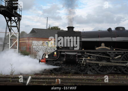 Front end of a steam engine, (class 5mt) juxtaposed against modern graffiti as it pull out of Bristol Temple meads - Stock Image