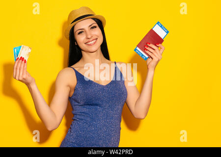 Young smiling excited woman student holding passport boarding pass ticket and credit card isolated on yellow background. Air travel flight - Image - Stock Image