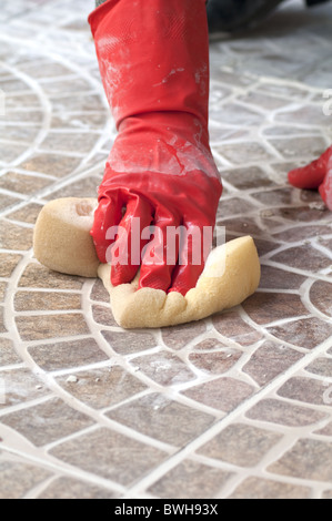 Close up of construction worker installing decorative tiles - Stock Image
