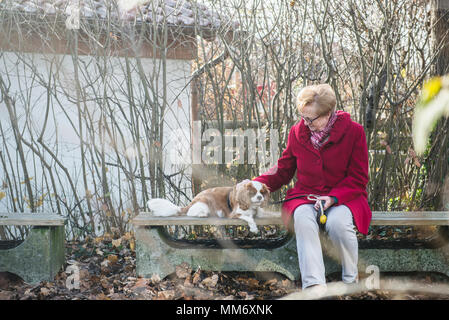 Old woman and her dog sitting outside on bench - Stock Image