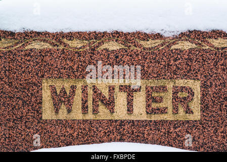 Red granite tombstone and snow in winter - Stock Image