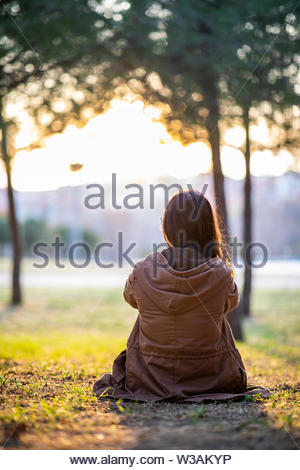 Beautiful woman sitting on the grass in a park during fall sunset with copy space - Stock Image