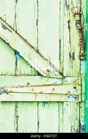 The hinge of a weathered green wooden gate - Stock Image