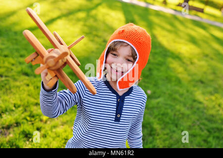 boy in orange helmet pilot playing in toy wooden plane against grass background - Stock Image