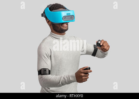 Dark skinned confident man with a short stubble, dressed in white pullower, wearing blue mobile virtual reality headset holding hands as if he is driv - Stock Image