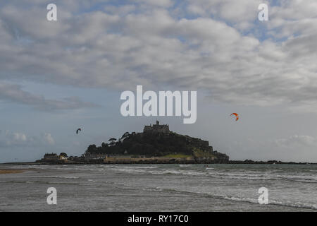 Marazion, Cornwall, UK. 11th March 2019. UK Weather.  Kite surfers were on the beach this afternoon at Marazion, making the most of the windy conditions, ahead of storm Gareth Credit: Simon Maycock/Alamy Live News - Stock Image
