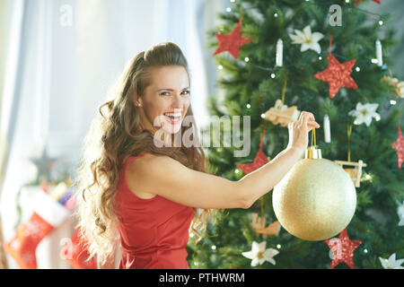 happy modern woman in red dress near Christmas tree hanging big gold Christmas ball on Christmas tree - Stock Image