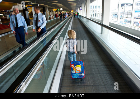Three year old boy on his way to departure hall aT Schiphol Airport in Netherlands, Europe - Stock Image