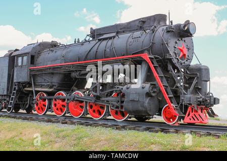 Old Soviet locomotive standing on the siding - Stock Image
