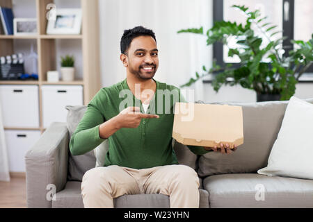 indian man with box of takeaway pizza at home - Stock Image